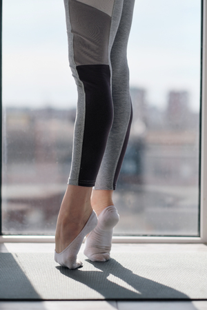 Close-up of female legs in sportswear and socks. Training of dance moves and stretching on the balcony against the window. Concept of home sport and active lifestyle.