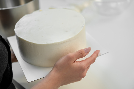 White smooth cylindrical cake blank in the hands of the pastry chef. Close-up.