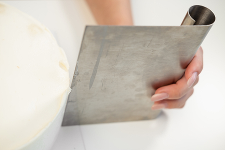 White smooth cylindrical cake blank. The confectioner creates the shape of a pastry spatula. Close-up.