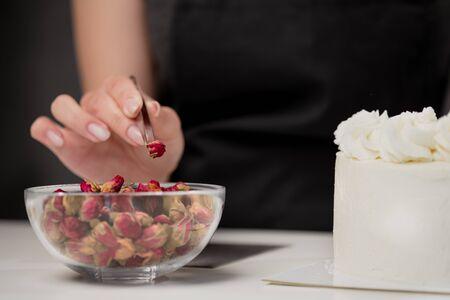 Una atractiva joven pastelera morena decora un pastel blanco con pequeñas flores rojas de comida rosa con pinzas. Sobre un fondo gris oscuro.