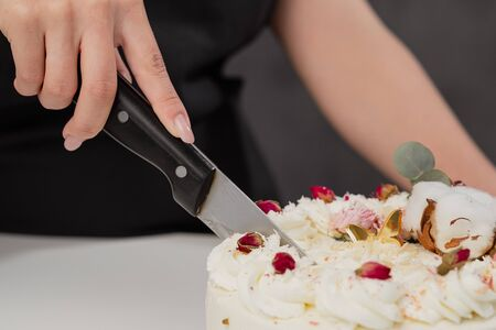 A condater cuts a beautiful fresh decorated white cake with a large knife on the table.