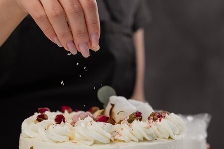 The condater sprinkles the cake with grated almonds and coconut. Close-up of a hand and pouring crumbs. White cake on a gray background. Banco de Imagens