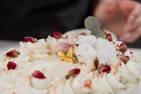 Der Condator bestreut den Kuchen mit geriebenen Mandeln und Kokosnuss. Nahaufnahme einer Hand und Krümel gießen. Weißer Kuchen auf grauem Hintergrund. Standard-Bild