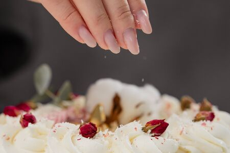 The condater sprinkles the cake with grated almonds and coconut. Close-up of a hand and pouring crumbs. White cake on a gray background. 版權商用圖片