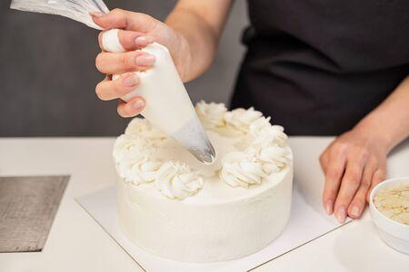 Konditor bei der Arbeit. Sahnetorte dekorieren. Kochtisch bereitet einen Kuchen auf grauem Hintergrund vor.