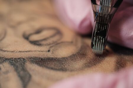 Close-up of a tattoo needle. The process of the tattoo master. Pink womens protective gloves. Tattoo sketch nun. Imagens