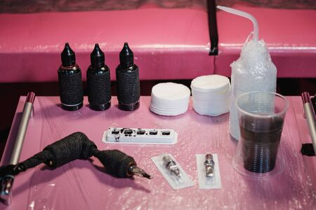Close up of tattoo master tools. Needles, inks, petroleum jelly and disinfectant liquid. On a pink and white background. Concept tattoo studio.