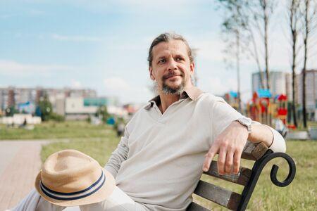 Ein attraktiver älterer 50-jähriger Mann mit langen Haaren im Schwanz sitzt in einem öffentlichen Garten auf einer Bank. Warmer Sommertag, hellbeige Kleidung. Lächelt und ruht. Standard-Bild