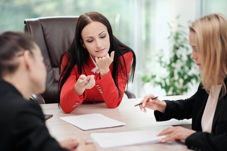 Three young attractive women in business suits are sitting at a desk and discussing workflows. Head and subordinates. Working team of professionals and colleagues. Feminism and feminine power. Banco de Imagens
