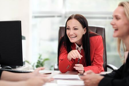 Three young attractive women in business suits are sitting at a desk and discussing workflows. Head and subordinates. Working team of professionals and colleagues. Feminism and feminine power. Stock fotó