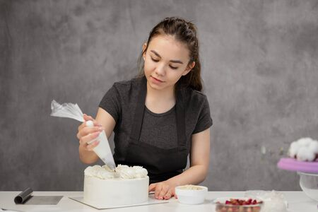 Confectioner at work. Cream cake decorating. Cook table preparing a cake on a gray background.
