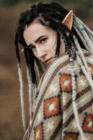 Beautiful young woman with elf ears, dreadlocks and an ethnic poncho, with painted face. Posing against a sandy career or desert. Fashion photography. Stock Photo