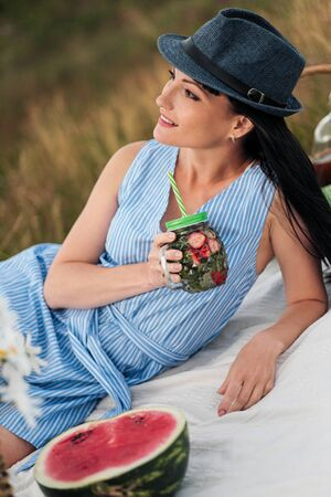 A young beautiful woman in hat and dress is drinking lemonade from a glass jar, sitting on plaid on green grass. Picnic basket, bouquet of daisies, watermelon. Concept of relexation in nature.