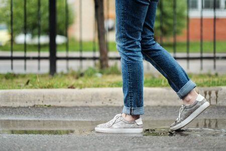 Close-up of feet in sneakers are walking through the puddles on the pavement. Rain and cloudy weather.
