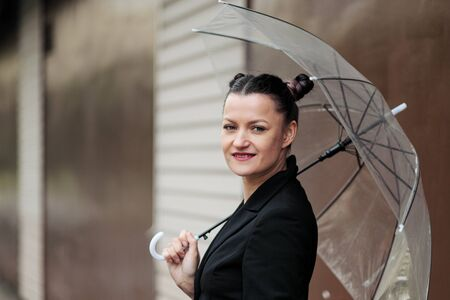 A young attractive woman in a black jacket and blue jeans posing outdoor against the background of the building. Holds a transparent umbrella. Rainy weather. Imagens