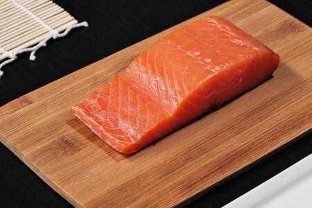 Pesce rosso, salmone affumicato su un tagliere di legno. Ingredienti per panini e sushi. Il concetto di cucina.