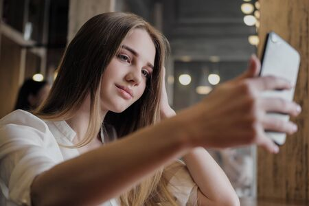 A young beautiful brunette girl in a loft-style cafe sits at a table by the window, drinks coffee and uses a smartphone, calls, takes pictures and types a message. Stock Photo - 128907598