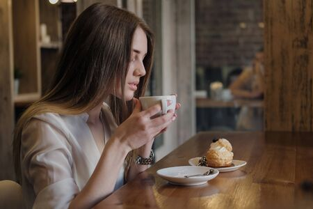 Young beautiful brunette girl in a loft style cafe sits at a table by the window, drinks coffee and eats a dessert cake. Against the background of a window and a brick wall. Stock Photo - 128907599