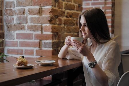 Young beautiful brunette girl in a loft style cafe sits at a table by the window, drinks coffee and eats a dessert cake. Against the background of a window and a brick wall.
