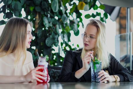 Two young beautiful girls, blonde and brunette, sit at a table in a cafe or restaurant. Communicate and talk, drink blue and red cocktails drinks. Cool drinks, lemonade. 写真素材