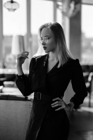 Black and white young beautiful blond woman with glasses sits at the bar in a yellow interior. Drinks alcoholic cocktail with a straw and green mint. Night life. and rest at a party. 写真素材
