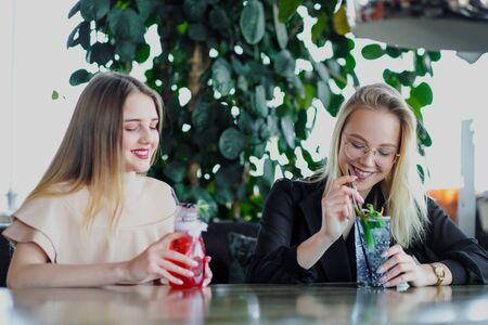 Two young beautiful girls, blonde and brunette, sit at a table in a cafe or restaurant. Communicate and talk, drink blue and red cocktails drinks. Cool drinks, lemonade.