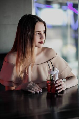 Young beautiful brown-haired girl in a nightclub with neon lights sits by the glass and drinks a red cocktail, reflected in the glass.