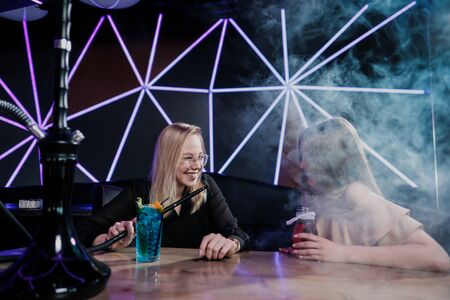 Two young smart beautiful girls in dresses sit at a table in a nightclub or hookah. They smoke hookah and smoke and drink cocktails from glasses with tubules, talk and laugh. Take a selfie on the phon 写真素材