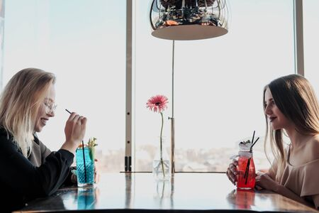 Two young smart beautiful girls in dresses sit at a restaurant table opposite a large window. Drink red and blue cocktails from glasses with tubules, communicate and laugh.