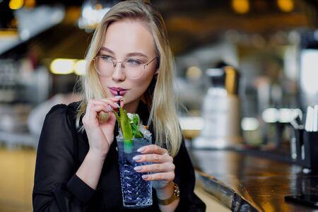 眼鏡をかけた若い美しいブロンドの女性は、黄色いインテリアのバーに座っています。ストローとグリーンミントのアルコールカクテルを飲みます。ナイトライフ。そしてパーティーで休む。