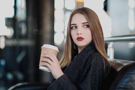 A young beautiful brunette girl in a gray coat is sitting on a bench waiting. Drinking coffee and holding a paper cup with a drink. Gray blurred background. 写真素材