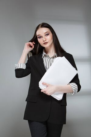 Young beautiful female fashion model in a business stylish suit on a rerom background. Holds a stack of papers and a pen. Businesswoman.