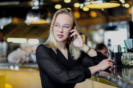 A young beautiful blond woman with glasses sits at the bar in a yellow interior. Drinks alcoholic cocktail with a straw and green mint. Night life. and rest at a party.