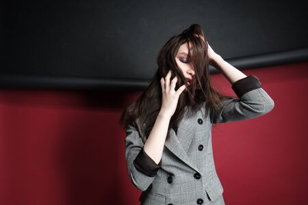 Young beautiful female fashion model in a business stylish suit on a red and black background. Stands and sits. Banco de Imagens
