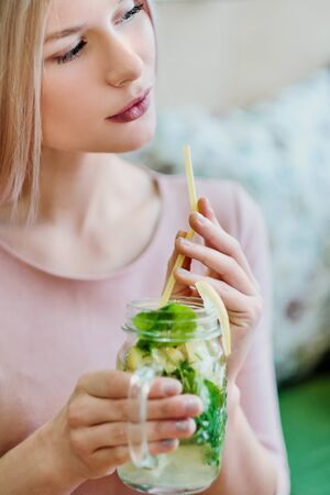Young beautiful blonde girl in a pink dress sits at a cafe table, drinks lemonade from a glass jar and uses a smartphone. Close up lips and hands. Banco de Imagens