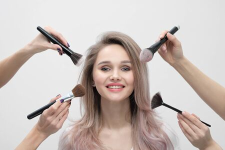 Make up salon, makeup artist work. Four hands with tassels and the face of a smiling beautiful blonde girl. Stock Photo