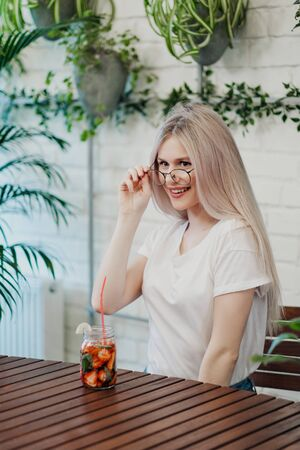 Young beautiful athletic woman blonde in glasses sits at a table in a green cafe and drinks strawberry lemonade from a glass jar. Smiles and laughs. 스톡 콘텐츠