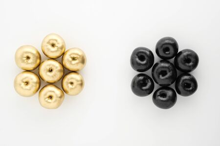 Golden and black apples on white background. Two groups, comparison and opposition. The concept of oil prices.