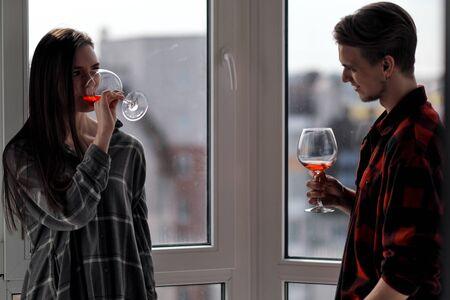 Junges schönes Paar in karierten Hemden auf dem Balkon eines mehrstöckigen Gebäudes. Wein trinken und probieren, Kontakte knüpfen, lachen und umarmen.