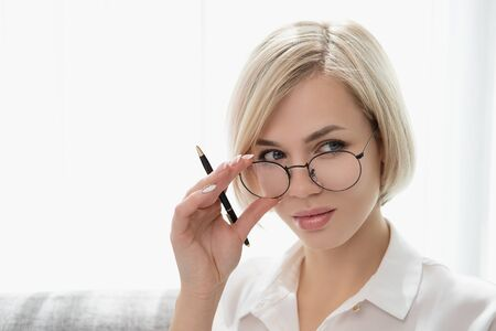 Young beautiful blonde girl with short hair in a white shirt and glasses close-up holds a pen in her hands. Holds glasses with his hands and looks out from under the glasses.