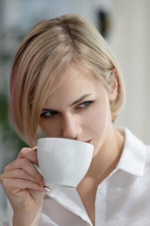 Young beautiful blonde woman in white shirt and glasses is sitting on the sofa in bright office against the window. Holds a white cup and drinking coffee or tea in a working break. Relaxation concept.