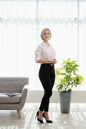 Young beautiful blonde girl with short hair in a white shirt is standing in the office. Office worker, business.