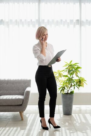 Young beautiful blonde girl with short hair in a white shirt is standing bright in the office against the window. Holds a notebook and smartphone. Talking on the phone. Office worker, business.