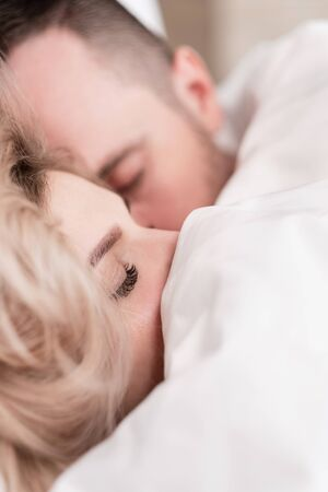 A married couple, a man and a woman, are lying in bed, hugging and sleeping on white bedding. Hiding their faces under the blanket and looking out.