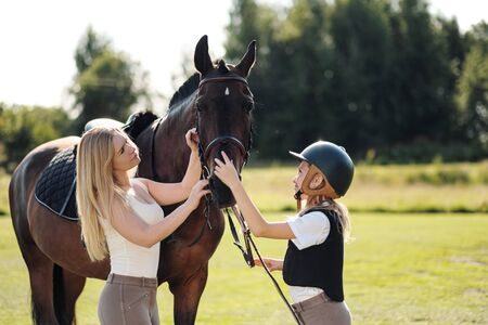 Mother and daughter riders and jockeys on a green field hug a brown horse. Mentor and student.
