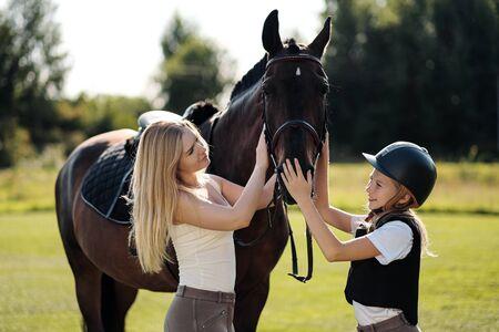 Madre e hija jinetes y jinetes en un campo verde abrazan a un caballo marrón. Mentor y alumno.