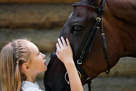 A teenage girl jockey stands next to a brown horse and hugs her. Against the background of a wooden wall stables on a green field.