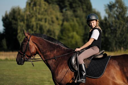 Mädchen Teenager Jockey sitzt auf einem braunen Pferd in der Natur. Dressurpferde, Reiterausbildung.