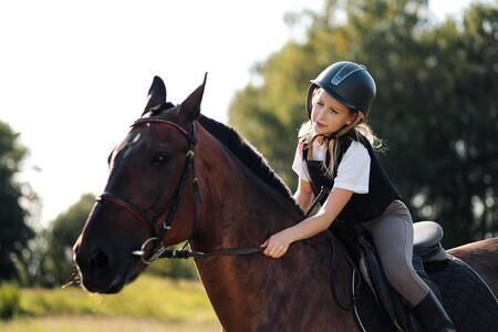 Girl teenager jockey sits on a brown horse, hugs and strokes her. Riders love of a horse. Reklamní fotografie