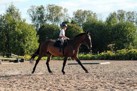 Mädchenjugendlicher Jockey trainiert auf dem Feld und am Hippodrom. Galopp und Trab.